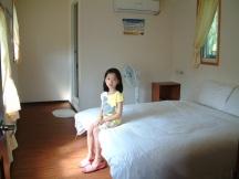 Ann 坐在二樓主臥室留影。這一幢綠色建築自然採光、通風,環境極佳。