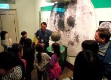 導覽志工正在介紹月球與地球的互動關係。Ann 回答了志工老師的問題:「地球會自轉,為何地球上總是只能看見月球的單側?」