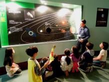 導覽志工正在介紹太陽系中位於火星、木星之間的小行星帶,由於受到木星強大的吸引力,使得這些漂流的小行星無法聚合成為單一行星~