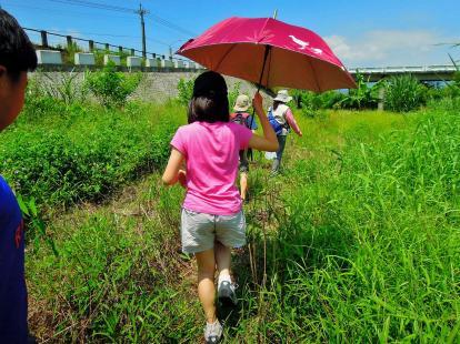 「員山生態教育館」的領隊帶著我們走下雜草叢生的河堤,觀察水門控制與溝渠~